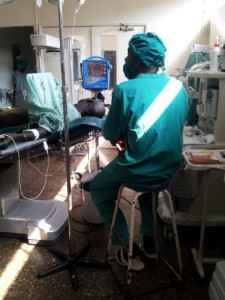 A patient undergoing a hernia repair. His hospital robe is used as a screen.